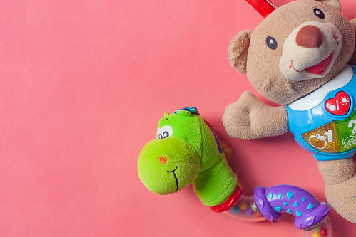 Child rattles. Bear and snake toys for newborn babies on the pink background. View from above. Copy space for text.