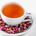 White Cup of tea and dried rose buds in saucer