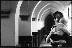 TeriWeddingFilm_077 (Johnny Martyr) Tags: church woman mother mom concentric lines parallel composition moment baby child quiet care tender love affection caring repeat repetitive redundant arch arches standing position nikon nikkor kodak p3200 tmax hc110 hc110b grain grainy film 35mm bw 85mm dark light shadow available existing natural window cathedral religious religion wedding photojouralism photojournalist documentary real candid unstaged