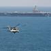 An MH-60S Sea Hawk helicopter flies toward the aircraft carrier USS John C. Stennis