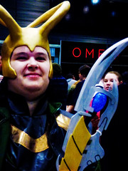 He Is So Proud of His Weapon (Steve Taylor (Photography)) Tags: weapon helmet blue yellow red green gold happy newzealand nz southisland canterbury christchurch armageddonexpo addington armaggedon costume spear