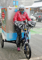 Winter Sucks (HereInVancouver) Tags: woman bicycle delivery street denmanstreet snowfall snowflurries candid streetphotography vancouverswestend winter canong9x city urban wintersucks vancouver bc canada
