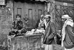 Sana'a Street (Rod Waddington) Tags: middle east yemen yemeni sanaa city streetphotography street seller selling chat khat drug natural men blackandwhite mono monochrome urban islam group outdoor culture cultural