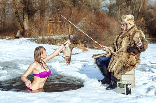 Young girl and elderly fisherman on winter fishing.
