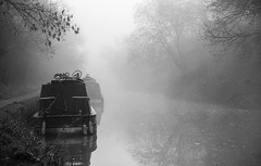 Narrowboats in Early Morning Mist (Rookie Phil) Tags: outdoor daytime spring canal water canalside narrowboats earlymorning dawn mist fog reflections calmwater placidscene tranquility rustic bucolic trees canalpath picturesque moody atmospheric bw blackandwhite monochrome fujifilmxt3 xt3 fujinonxf1655mmf28 xf1655mmf28 serene