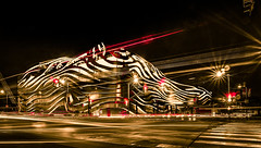 Exterior of Petersen Automotive Museum at night in november with car trails (DigiDreamGrafix.com) Tags: twilight museum automotive losangeles westcoast hotrods fastcar red sky illuminated metal steel pattern cloud sunset architecture city downtown cars organic street landmark streetlight waves lighting contemporary racecar california la wilshire night lights