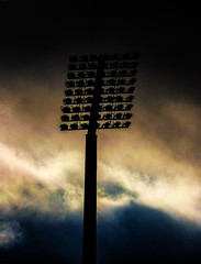 Lighting Up the Sky (Steve Taylor (Photography)) Tags: architecture light black blue brown metal newzealand nz southisland canterbury christchurch glow silhouette winter cloud sky addington floodlight rugbyground