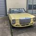 Oldtimer Auto Mercedes 200D in hellgelb steht vor Garageneinfahrt