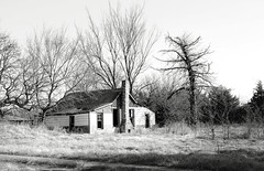 Bourbon County, Kansas (unknown quantity) Tags: abandonedhouse shadows blackandwhite ruts baretrees winter sky openwindows opendoorway brokenroof grass monochrome fadedpaint weathered
