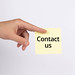 Hand holding note with Contact us text