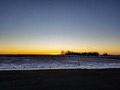 Along the road sunset. (darletts56) Tags: sky sun sunset dusk evening night snow winter tree trees farm yard field fields prairie orange gold golden white ice icy barn pole post grass saskatchewan canada road country flat silhouette yellow black
