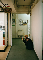 """""""gossip"""" just around the corner... (hugo poon - one day in my life) Tags: fujifilm klasse film fujifilmsuperiaxtra400 colours hongkong causewaybay foomingstreet aged 60s architecture shopping solitude girl browse smartphone gossip sign lobby corridor happyplanet asiafavorites"""